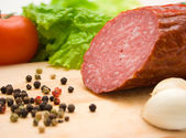 Macro of cut salami, pepper seeds and vegetables — Stock Photo