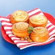 Four cinnamon rolls on red plate — Stock Photo