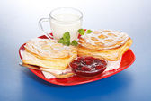 Breakfast: two sour cherry cakes, milk and jam on plate — Stock Photo