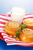 Three cinnamon rolls and jug of milk on red plate — Stock Photo