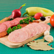 Salami and sausage slices and vegetables — Stock Photo