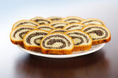 Slices of poppy seed rolls on plate — Stock Photo