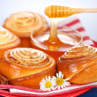 Pouring honey behind fresh cinnamon rolls — Stock Photo