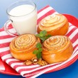 Three cinnamon rolls and jug of milk on red plate — Stock Photo #19664611