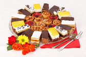 Various sweet cakes on round plate — Stock Photo