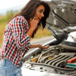 Woman calling service in front of broken car — Stock Photo