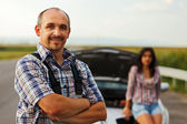 Repairman and woman driver in front of broken car — Stock Photo