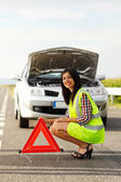 Woman placing emergency triangle — Stock Photo