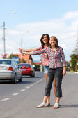 Girls hitch-hiking — Stock Photo