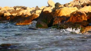Side view of sea waves breaking on rocks in sunset