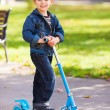 Happy boy with scooter in playground — Stock Photo