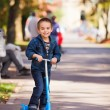 Joyful kid riding a scooter — Stock Photo