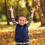 Joyful kid playing with leaves — Stock Photo