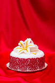 White fondant cake decorated with red lace and edible candy lily — Stock Photo