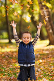 Joyful kid playing with leaves — Stock Photo