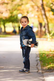 Kid playing outdoors with skateboard — Stock Photo