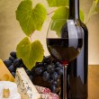 Stock Photo: Red wine with grape and cheese snack