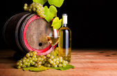 White wine and grapes in front of old barrel — Stok fotoğraf