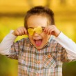 Happy kid playing with autumn leaves — Stockfoto