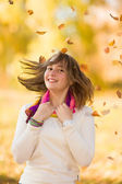 Joyful teen girl having fun in falling leaves — Stock Photo