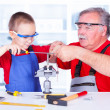 Grandfather teaching grandchild rasping — Stock Photo #35718775