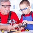 Grandfather and grandchild measuring bolt — Stock Photo