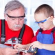 Stock Photo: Grandfather and grandchild measuring bolt