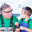 Stock Photo: Grandfather and grandchild using multimeter