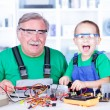 Stock Photo: Happy grandfather and grandchild working in workshop
