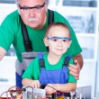 Stock Photo: Proud grandfather with grandchild in workshop
