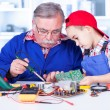 Grandfather explaining to grandchild how soldering works — Stock Photo