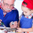 Grandfather showing PCB soldering to grandchild — Stock Photo #35718867