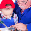 Grandfather teaching grandchild soldering with iron — Stock Photo