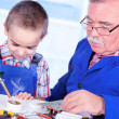 Stock Photo: Grandfather teaching grandchild to use soldering resin