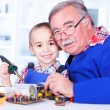 Happy grandfather and grandchild working together in workshop — Stock Photo