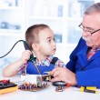 Stock Photo: Grandfather teaching grandchild working with soldering iron