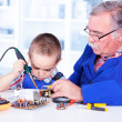 Grandfather teaching grandchild working with soldering iron — Stock Photo