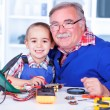 Stock Photo: Happy grandfather and grandchild working together in workshop