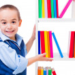 Stock Photo: Little boy offering books on shelf