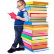 Stock Photo: Little boy reading near big stack of books