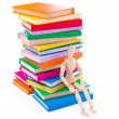 Wooden dummy puppet sitting on books — Stock Photo