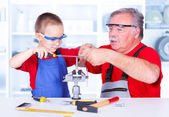 Grandfather teaching grandchild rasping — Stock Photo