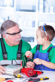 Grandfather and grandchild using multimeter — Stock Photo