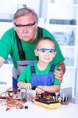 Proud grandfather with grandchild in workshop — Stock Photo