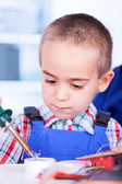 Child playing with soldering iron and resin — Stock Photo
