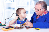 Grandfather teaching grandchild working with soldering iron — ストック写真