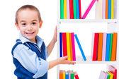 Little boy offering books on shelf — Stock Photo