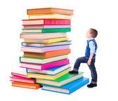 Menino olhando para empilhados livros grandes — Fotografia Stock