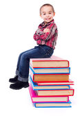 Little boy sitting on stacked colorful books — Stock Photo
