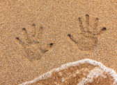 Handprint on sand being washed away — Stock Photo